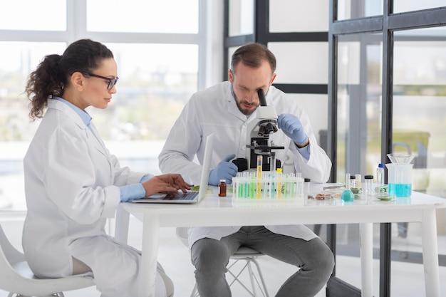 Middelgrote wetenschappers die laboratoriumjassen dragen