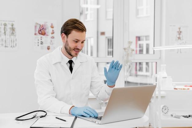 Middellange geschoten arts die aan laptop werkt