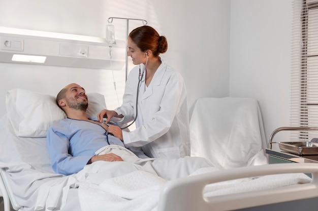 Middellange geschoten arts die een stethoscoop gebruikt