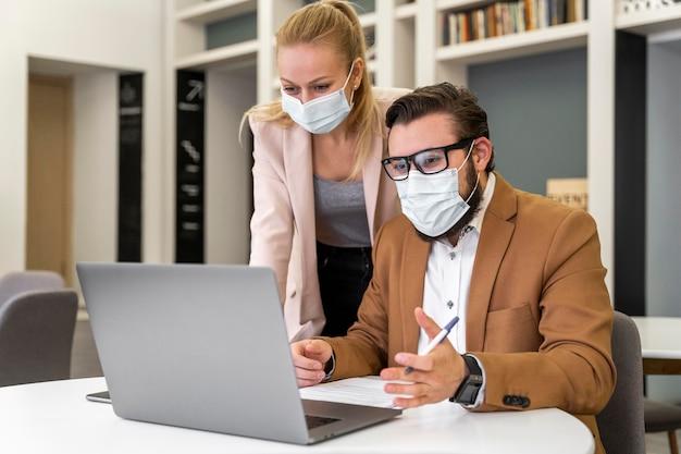 Middellange geschoten collega's die maskers dragen