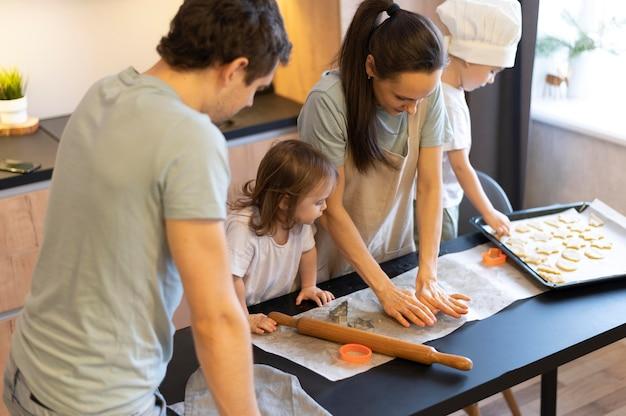 Middellange geschoten familie die koekjes klaarmaakt