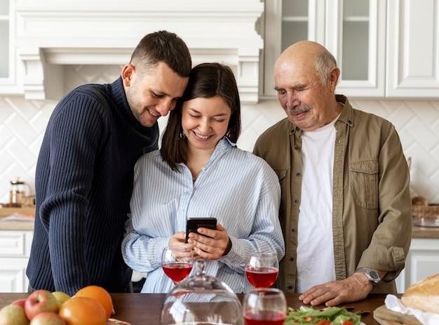 Middellange geschoten familie die naar telefoon kijkt