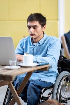 Middellange geschoten gehandicapte man aan het werk op laptop