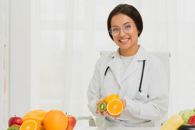 Middellange geschoten gelukkige arts met sinaasappel en kiwi