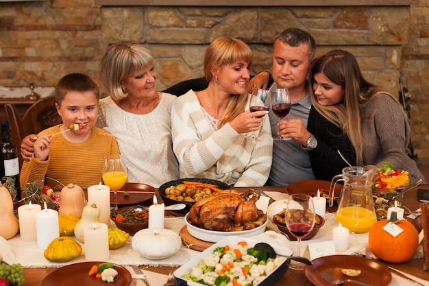 Middellange geschoten gelukkige familie tijdens het diner