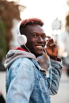 Middellange geschoten gelukkige kerel die met hoofdtelefoons weg kijken