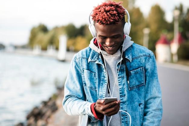 Middellange geschoten gelukkige kerel die zijn smartphone bekijken