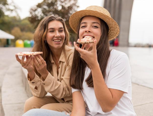Middellange geschoten gelukkige meisjes die pizza eten