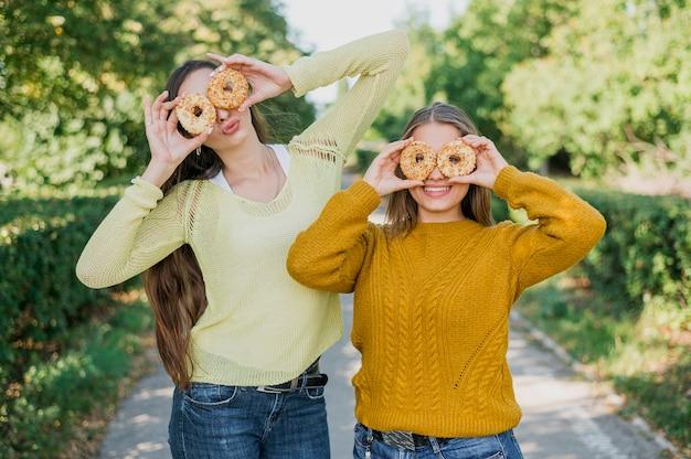 Middellange geschoten gelukkige meisjes met donuts