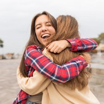 Middellange geschoten gelukkige vrienden die buitenshuis knuffelen