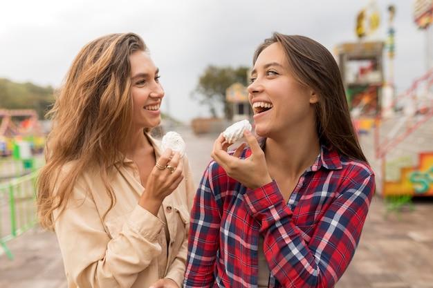 Middellange geschoten gelukkige vrienden met snoep