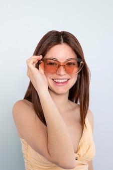 Middellange geschoten gelukkige vrouw die zonnebril draagt