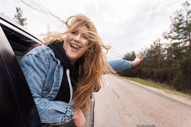 Middellange geschoten gelukkige vrouw in auto
