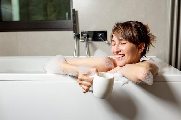 Middellange geschoten gelukkige vrouw in de badkuip