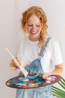 Middellange geschoten gelukkige vrouw met het schilderen van palet