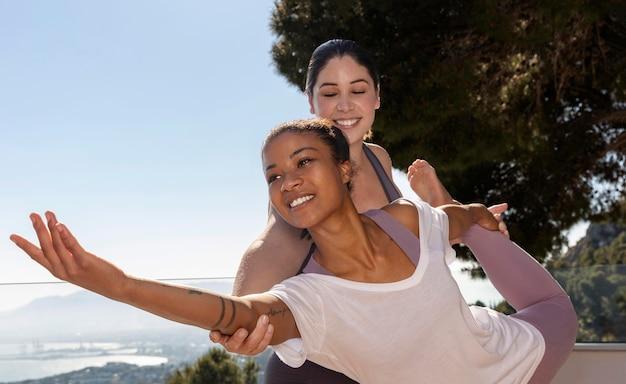 Middellange geschoten gelukkige vrouwen die yoga doen