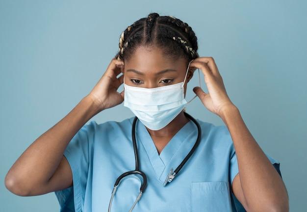 Middellange geschoten gezondheidswerker die masker draagt