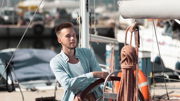 Middellange geschoten jongeman op boot