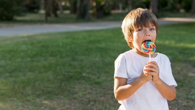 Middellange geschoten jongen die lolly eet
