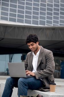 Middellange geschoten man aan het werk op laptop Gratis Foto
