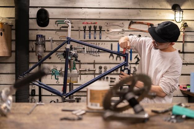 Middellange geschoten man die fiets repareert
