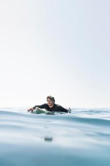 Middellange geschoten man met surfplank
