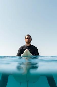 Middellange geschoten man zittend op een surfplank