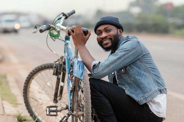 Middellange geschoten mens die dichtbij fiets stelt
