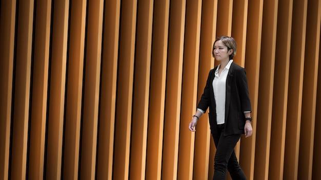 Middellange geschoten moderne vrouw aan het wandelen