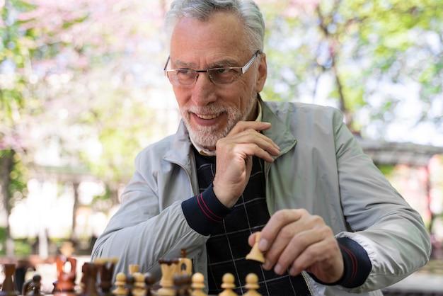 Middellange geschoten oude man aan het schaken