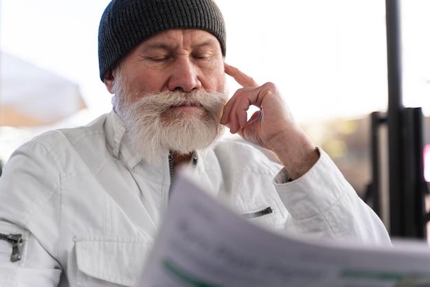 Middellange geschoten oude man die de krant leest