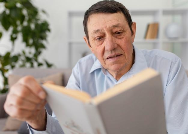 Middellange geschoten oude man die een boek leest