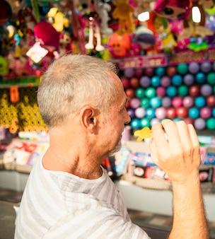 Middellange geschoten oude man die een spel speelt