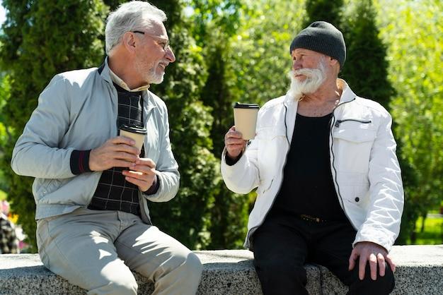 Middellange geschoten oude mannen met koffiekopjes