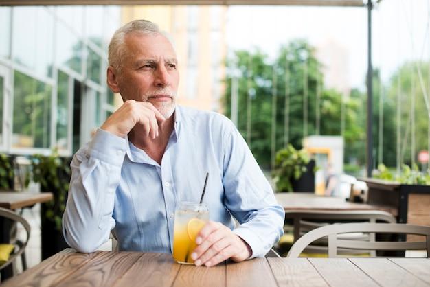 Middellange geschoten oude mens die bij restaurant denkt