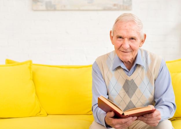 Middellange geschoten oude mens die een boek leest