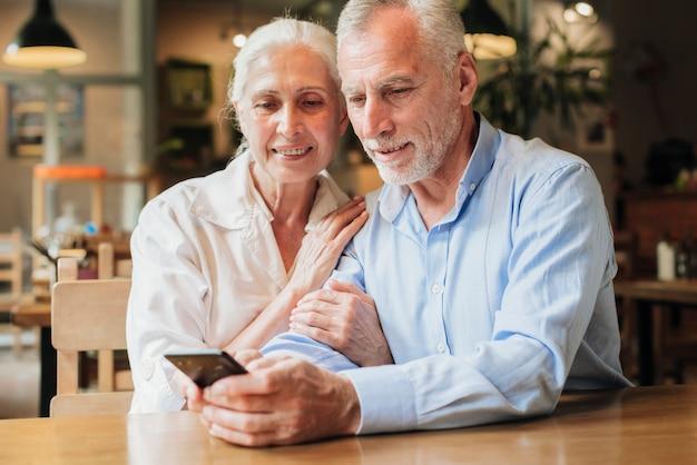 Middellange geschoten oude mensen met smartphone