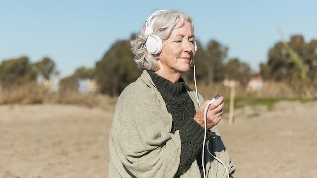 Middellange geschoten oude vrouw die aan muziek luistert