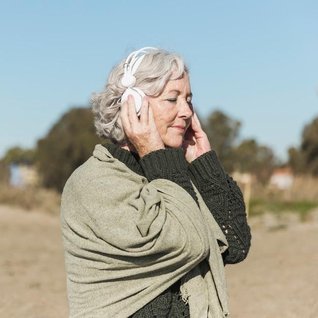 Middellange geschoten oude vrouw met hoofdtelefoons
