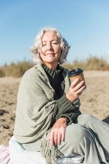 Middellange geschoten oude vrouw met koffiekop