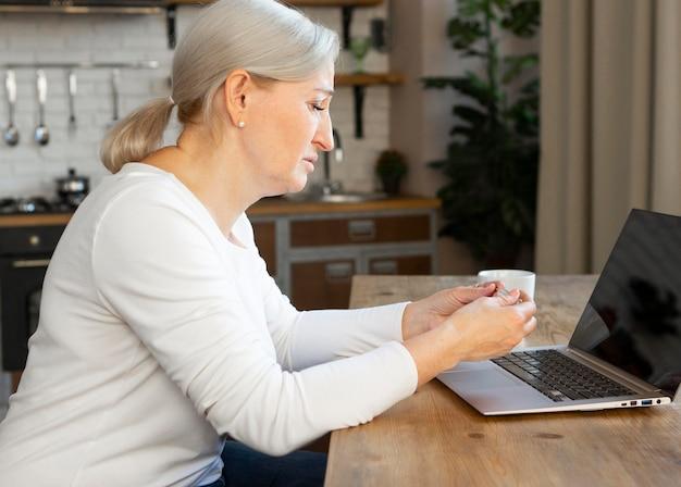 Middellange geschoten oude vrouw met laptop