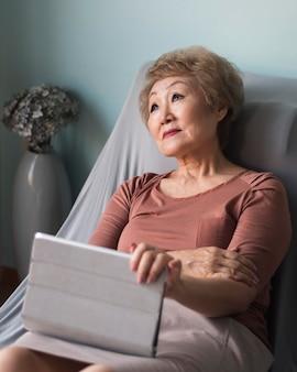Middellange geschoten oude vrouw met tablet