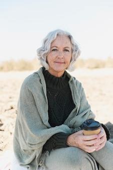 Middellange geschoten oude vrouw op het strand