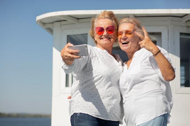 Middellange geschoten oudere vrouwen die selfie maken
