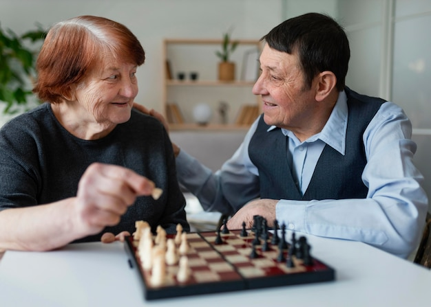 Middellange geschoten ouderen die schaken