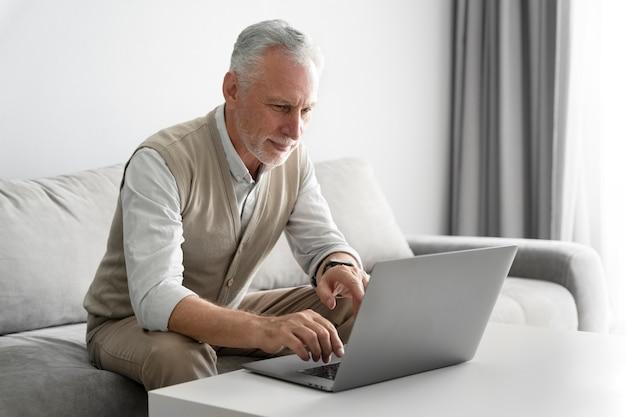 Middellange geschoten senior man met laptop