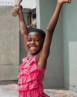 Middellange geschoten smiley meisje met bezem