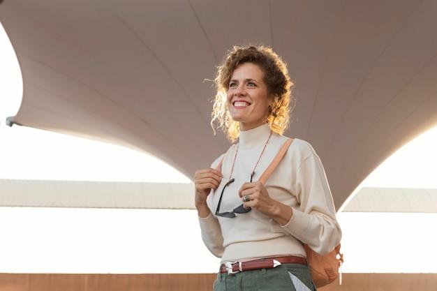 Middellange geschoten smiley vrouw reiziger