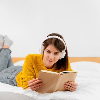 Middellange geschoten smileyvrouw die in bed leest