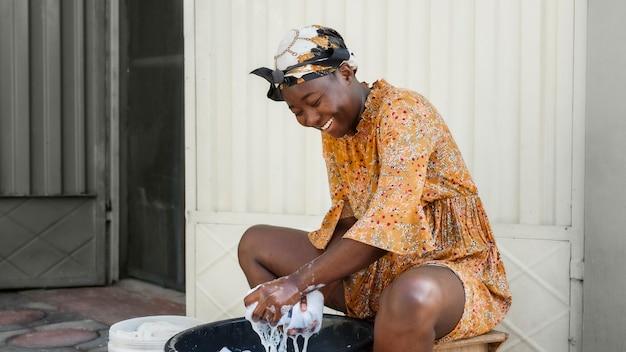 Middellange geschoten smileyvrouw die kleren wast